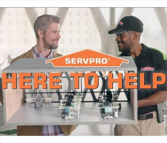 "SERVPRO employee and man talking with ""HERE TO HELP"" over them"