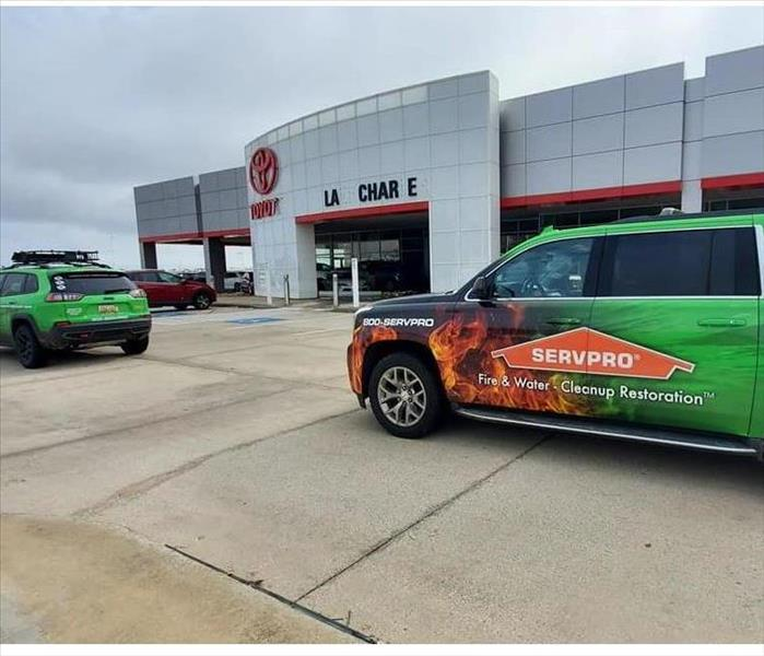 Two SERVPRO vehicles outside of damaged building